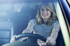 La mujer que conduce el coche en un pánico Fotografía de archivo