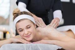 La mujer que consigue la sal exfoliating friega masaje en el ` s del cosmetólogo fotografía de archivo
