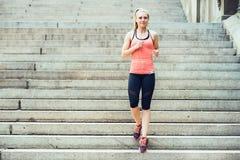 La mujer que corre en pasos en el Central Park de Nueva York escucha la música y la ropa del deporte que lleva en el tiempo de ve foto de archivo