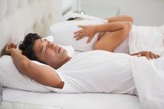 La mujer que cubre sus oídos como socio está roncando en alta voz Foto de archivo