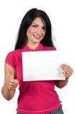 La mujer que da thumb-up y lleva a cabo una muestra en blanco Fotos de archivo
