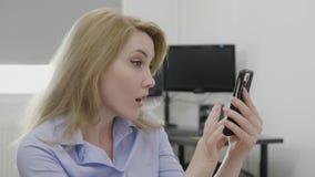 La mujer que deslizaba el contenido en su sensación del smartphone molestó dar una palmada a su concepto del facepalm del gesto d almacen de metraje de vídeo