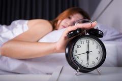 La mujer que duerme y despierta para apagar el despertador en mornin Fotos de archivo
