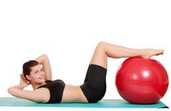 La mujer que el hacer se sienta sube con la bola del ejercicio Fotografía de archivo libre de regalías