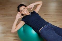 La mujer que el hacer se sienta sube con la bola suiza Foto de archivo libre de regalías