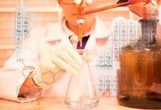 La mujer que es el científico está haciendo el experimento, la titulación del reactivo en el frasco Imágenes de archivo libres de regalías