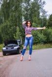 La mujer que espera para ayudar y que muestra manosea encima de cercano su coche con los dedos quebrado Imagenes de archivo