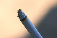La mujer que fuma un cigarrillo se sostiene al lado de los fingeres Imagenes de archivo