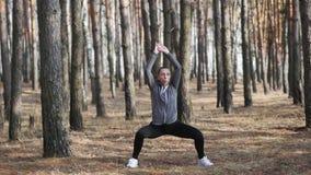 La mujer que hace aptitud ejercita al aire libre la muchacha que salta y que corre en parque metrajes