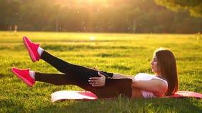 La mujer que hace crujidos abdominales ejercita en la estera de la aptitud en parque del verano en la cámara lenta en la puesta d almacen de metraje de vídeo