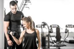 La mujer que hace el bíceps se encrespa en gimnasio con su instructor personal imagenes de archivo