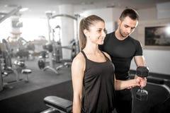 La mujer que hace el bíceps se encrespa en gimnasio con su instructor personal Foto de archivo