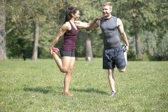 La mujer que hace estirar ejercita con el instructor personal en parque fotos de archivo