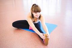 La mujer que hace estirar ejercita en el piso en el gimnasio imagen de archivo