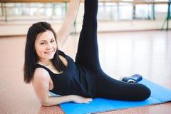 La mujer que hace estirar ejercita en el piso en el gimnasio foto de archivo