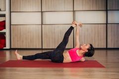 La mujer que hace la actitud de descanso de la yoga del dedo gordo, ésta estira ingles imágenes de archivo libres de regalías