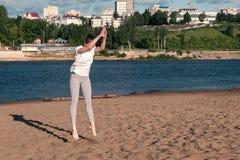 La mujer que hace los ejercicios se divierte en los bancos del río en la ciudad Salto foto de archivo