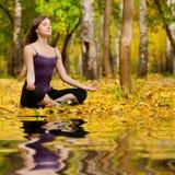 La mujer que hace yoga ejercita en el parque del otoño Imagenes de archivo