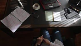 La mujer que hojea a través de los cuadernos en la tabla, artículos miente metrajes