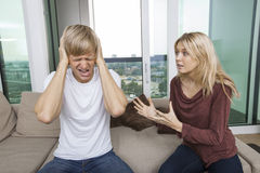 La mujer que intenta hablar como hombre grita hacia fuera en voz alta en sala de estar en casa Foto de archivo libre de regalías
