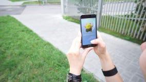 La mujer que juega Pokemon VA uso el teléfono elegante aumentado golpe app - Pokemon de cogida Drowzee de la realidad almacen de video