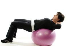 La mujer que la bola de la aptitud del entrenamiento de la base se sienta sube Fotografía de archivo libre de regalías