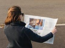 La mujer que lee a los franceses de Le Monde presiona el germen de las elecciones de Angela Merkel Fotografía de archivo