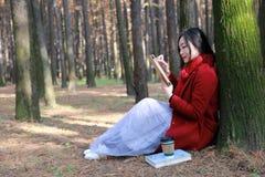 La mujer que lee un ebook o una tableta en un parque urbano, se sienta debajo de árbol Imagenes de archivo