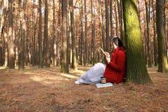 La mujer que lee un ebook o una tableta en un parque urbano, se sienta debajo de árbol Foto de archivo