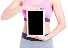La mujer que lleva a cabo deportes que llevan de la tableta negra de la pantalla lleva Fotos de archivo libres de regalías