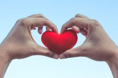 La mujer que lleva a cabo el corazón rojo en manos y hace forma del corazón de la mano Fotografía de archivo libre de regalías