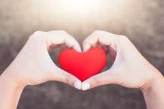 La mujer que lleva a cabo el corazón rojo y hace forma del corazón de la mano Imagen de archivo