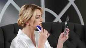 La mujer que lleva a cabo una mano sostiene un espejo y epilation el hacer encima de sus labios almacen de metraje de vídeo