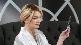 La mujer que lleva a cabo una mano sostiene un espejo y epilation el hacer encima de sus labios almacen de video