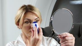 La mujer que lleva a cabo una mano sostiene un espejo y epilation el hacer encima de sus labios metrajes
