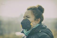 La mujer que lleva un anticontaminación real, contra la niebla y los virus la mascarilla fotos de archivo