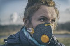 La mujer que lleva un anticontaminación real, contra la niebla y los virus la mascarilla fotos de archivo libres de regalías