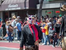 La mujer que lleva una máscara del diablo y que agrieta un azote camina abajo del st foto de archivo libre de regalías