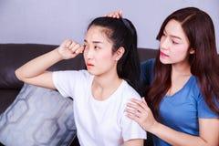 La mujer que llora, su amigo la está calmando en el sofá en casa Imagenes de archivo