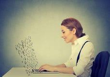 La mujer que mecanografía en el ordenador portátil con la pantalla hecha de alfabeto pone letras a volar para arriba Imagenes de archivo