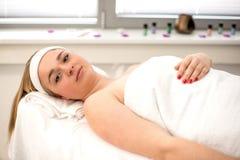 La mujer que mentía en la tabla del masaje prepaired para el tratamiento de la belleza Imagen de archivo libre de regalías