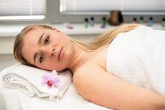 La mujer que mentía en la tabla del masaje prepaired para el tratamiento de la belleza Fotografía de archivo libre de regalías