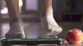 La mujer que mide el peso mediante escalas Mentiras próximas de la manzana La mujer salta con alegría El peso se convirtió menos almacen de video