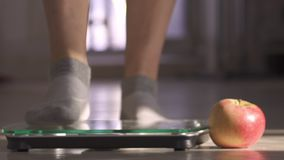 La mujer que mide el peso mediante escalas Mentiras próximas de la manzana El peso se convirtió menos almacen de video