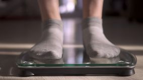 La mujer que mide el peso mediante escalas El peso se convirtió menos metrajes