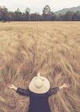 La mujer que miente con el sombrero oculta su cara en hierba amarilla del campo Relájese Imagenes de archivo