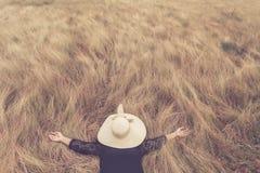 La mujer que miente con el sombrero oculta su cara en hierba amarilla del campo Relájese Imágenes de archivo libres de regalías