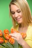 La mujer que mira abajo de la primavera florece tulipanes anaranjados Foto de archivo libre de regalías