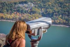 La mujer que mira a través de los prismáticos escénico pasa por alto en otoño Foto de archivo