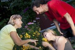 La mujer que muestra un par florece en el jardín imágenes de archivo libres de regalías